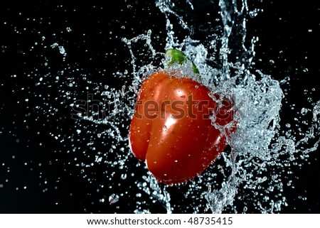 fresh red bell pepper gets hit by a water stream - stock photo