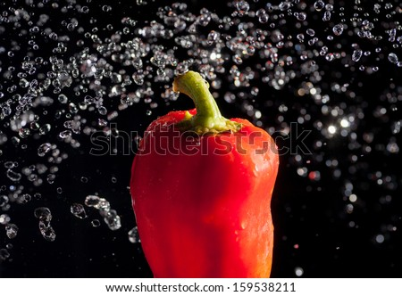 fresh red bell pepper gets hit by a water stream of drops - stock photo
