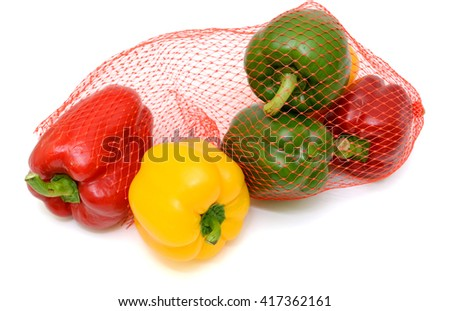 Fresh red bell pepper (in mesh bag) isolated on white background - stock photo