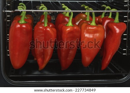 Fresh red bell roasting  in the oven - stock photo