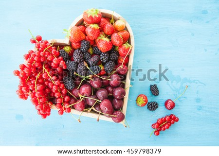 Fresh red berries in a heart-shaped tray on blue wooden background - stock photo