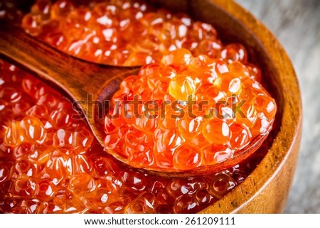 fresh red caviar in a wooden bowl with a spoonful closeup on a rustic background - stock photo