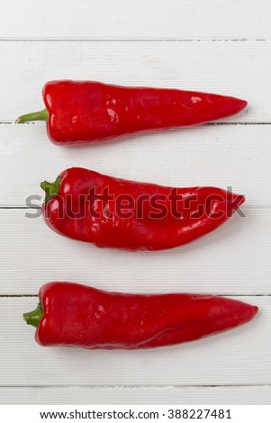 Fresh red cayenne peppers on a white wooden background. - stock photo