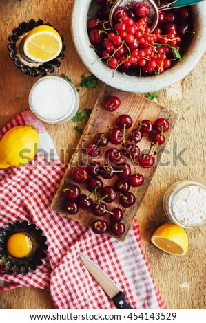 Fresh red cherries on a rustic  wooden table.  Ripe cherries i on wooden rustic background. Fresh cherries berries  on dark rustic wooden background - stock photo