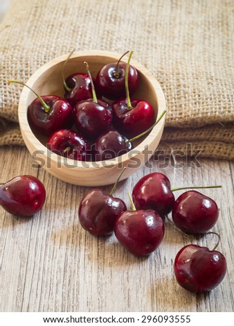 Fresh red cherries with water drops on wooden table - stock photo