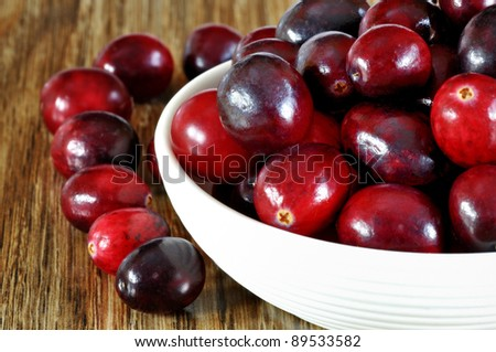 Fresh red cranberries in bowl on wooden background, selective focus - stock photo