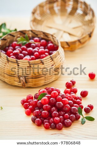 Fresh red cranberries with leaves in basket. Vertical view - stock photo