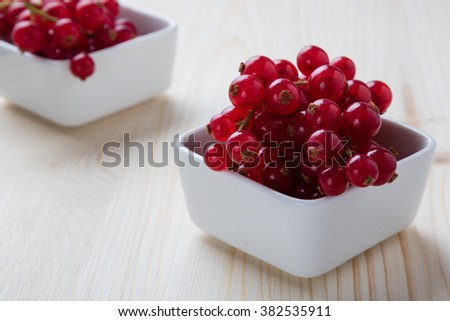 fresh red currant in white bowl on wooden table