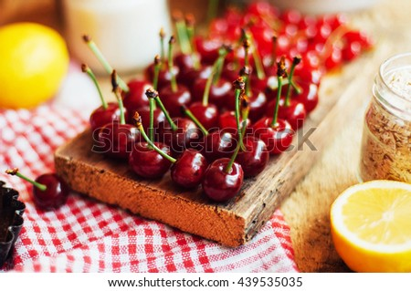 Fresh red currant on wooden table, bucket with red currant berries on a table.   Plate with Assorted summer berries, cherries,   garden fruit - stock photo