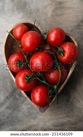 fresh red delicious tomatoes in heart-shape plate on old wooden tabletop. Selective focus, close up.  - stock photo