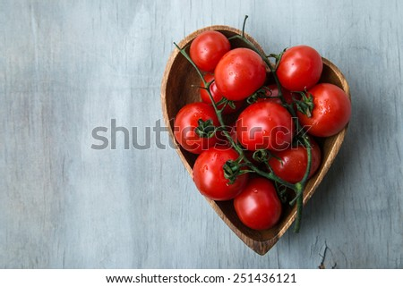 fresh red delicious tomatoes  in the heart shape wooden plate on an wooden tabletop with place for text. Selective focus, close up.  - stock photo