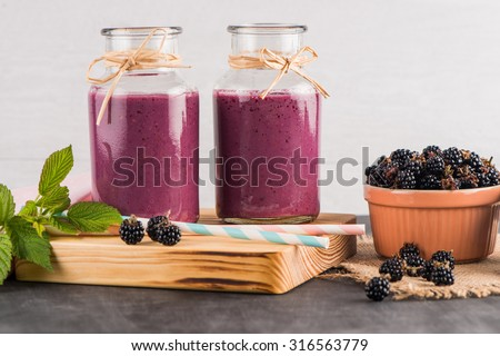 Fresh red fruits smoothie on vintage decorated  wooden table. - stock photo
