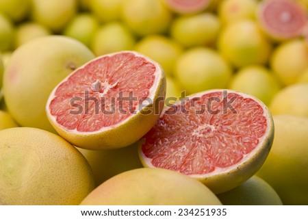 Fresh red grapefruit slices closeup, fruit background. Grapefruits on market for sale. background, wallpaper. - stock photo