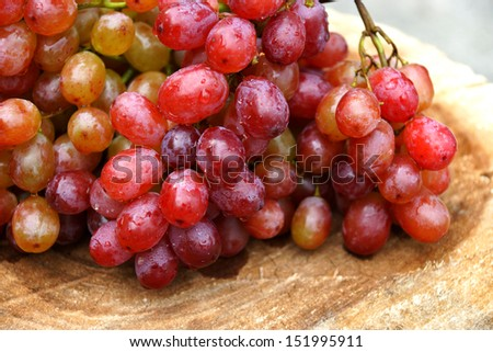 Fresh red grapes on brown wood.
