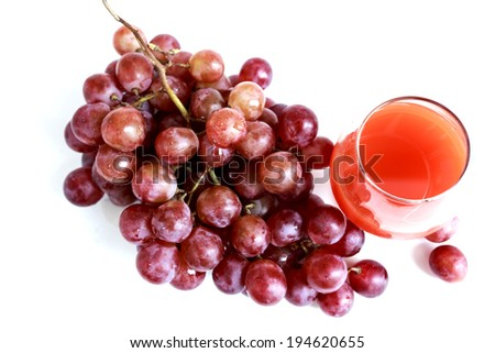 Fresh red grapes on white background with grape juice - stock photo