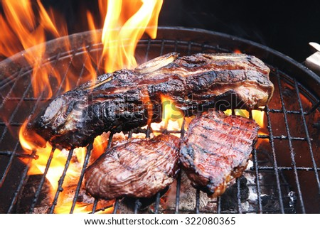 fresh red grilled beef meat fillet asado on deep round bbq grill over fire - stock photo