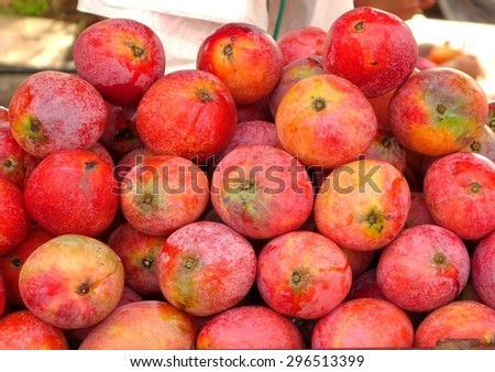 Fresh red Irwin mangoes for sale at an outdoor market - stock photo