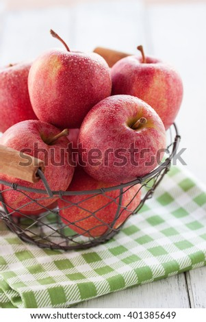 Fresh red juicy apples in a basket on a green textile on a wooden background, selective focus - stock photo