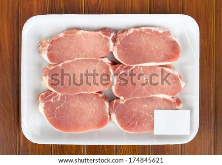 Fresh red meat packed in a poly bag. Isolated over wood - stock photo