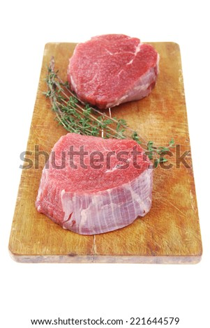 fresh red meat : two raw beef fillet chops on wooden board with small thyme twig ready to prepare . isolated over white background - stock photo
