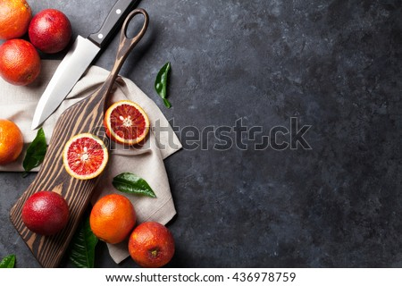 Fresh red orange fruits on stone table. Top view with copy space