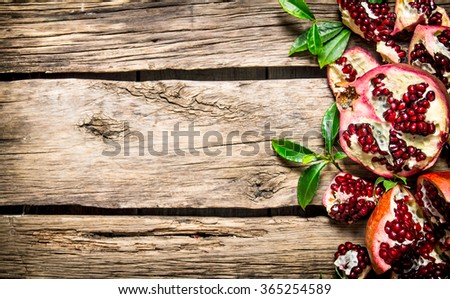 Fresh red pomegranate with leaves. On a wooden background. Free space for text . Top view - stock photo