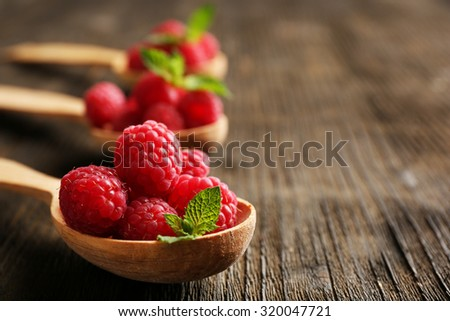 Fresh red raspberries in spoons on wooden table, closeup - stock photo