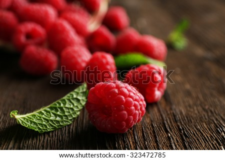 Fresh red raspberries on wooden table, closeup - stock photo