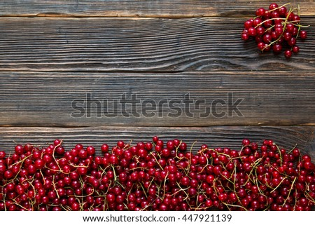 Fresh red ripe currants on a dark wooden background. Rustic style. - stock photo