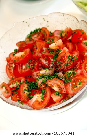 Fresh red ripe sliced tomato with a garnish of freshly chopped parsley in a glass serving dish - stock photo