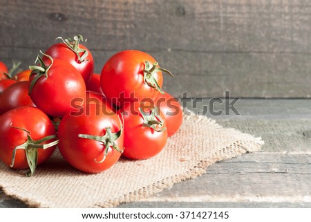 Fresh red ripe tomatoes on rustic wooden background - stock photo