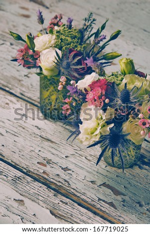 Fresh red roses and white flower bouquets in romantic style on grunge table, with space for text - stock photo