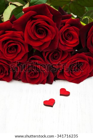Fresh Red roses and wooden hearts on a wooden background