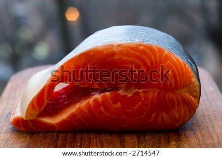 Fresh red salmon fish on wooden cooking desk(Shallow DOF) - stock photo