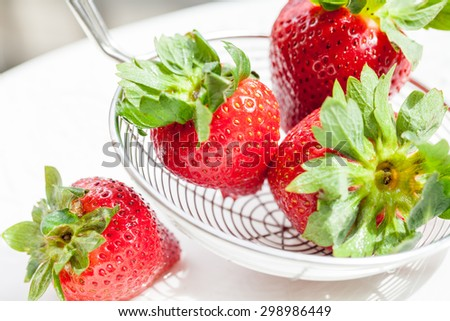 Fresh red strawberries on a colander on white background - stock photo