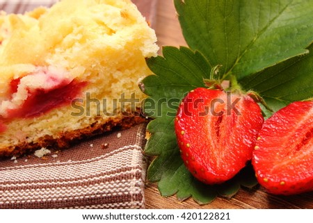 Fresh red strawberries with green leaves and piece of fresh baked yeast cake with crumble lying on wooden surface, concept of dessert