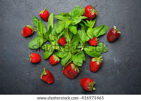 Fresh red strawberry with fresh mint on a dark background - stock photo