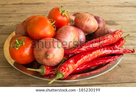 Fresh red tomato ,chilli,and onion in metal tray on table - stock photo