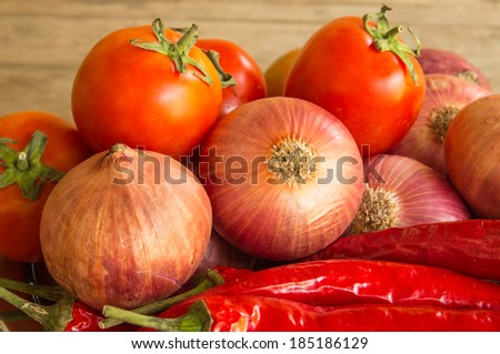 Fresh red tomato ,chilli,and onion in  table wooden background - stock photo