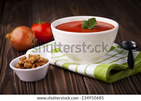 Fresh red tomato cream soup in white bowl. Dish and ingredients photography taken on old wooden table. - stock photo