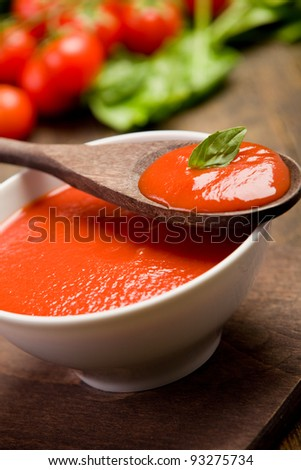 fresh red tomato sauce with basil leaf and wooden spoon - stock photo