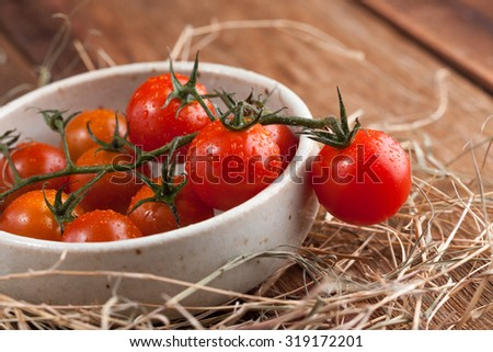 fresh red tomatoes in white bowl and hay on old wood background