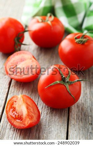 Fresh red tomatoes on grey wooden background