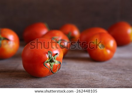 Fresh Red Tomatoes on Wooden Table in Natural Lighting. - stock photo
