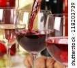 Fresh red wine pouring into a wine glass. Selective focus on the red wine. - stock photo