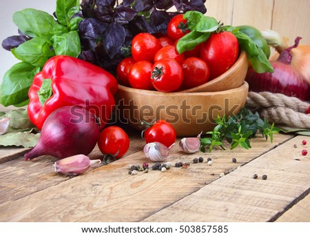 Fresh red, yellow and green peppers, tamaty, garlic and basil on a wooden background