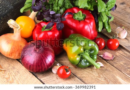 Fresh red, yellow and green peppers, tomatoes, garlic, spices and basil on a wooden background