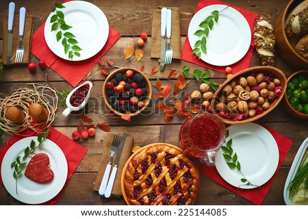 Fresh rennets, walnuts, pastry, jam, fruit drink and berries on wooden table - stock photo
