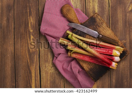 Fresh rhubarb on wooden cutting board. Rustic style, selective focus. Top view - stock photo