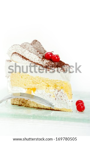 fresh ribes and whipped cream dessert cake slice with cocoa powder on top